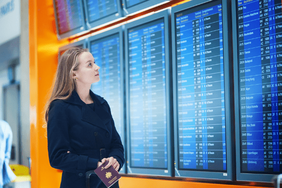 A young woman stands next to digital signage at the airport with her passport reviewing departure and arrival times.