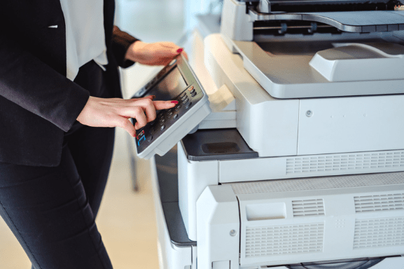Close up image of a professional woman using a multifunction system printer in an office