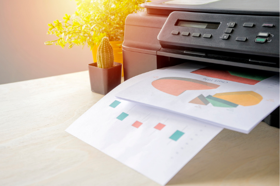 Close up of an office printer with colorful charts in the output tray to signify Managed Print Services.